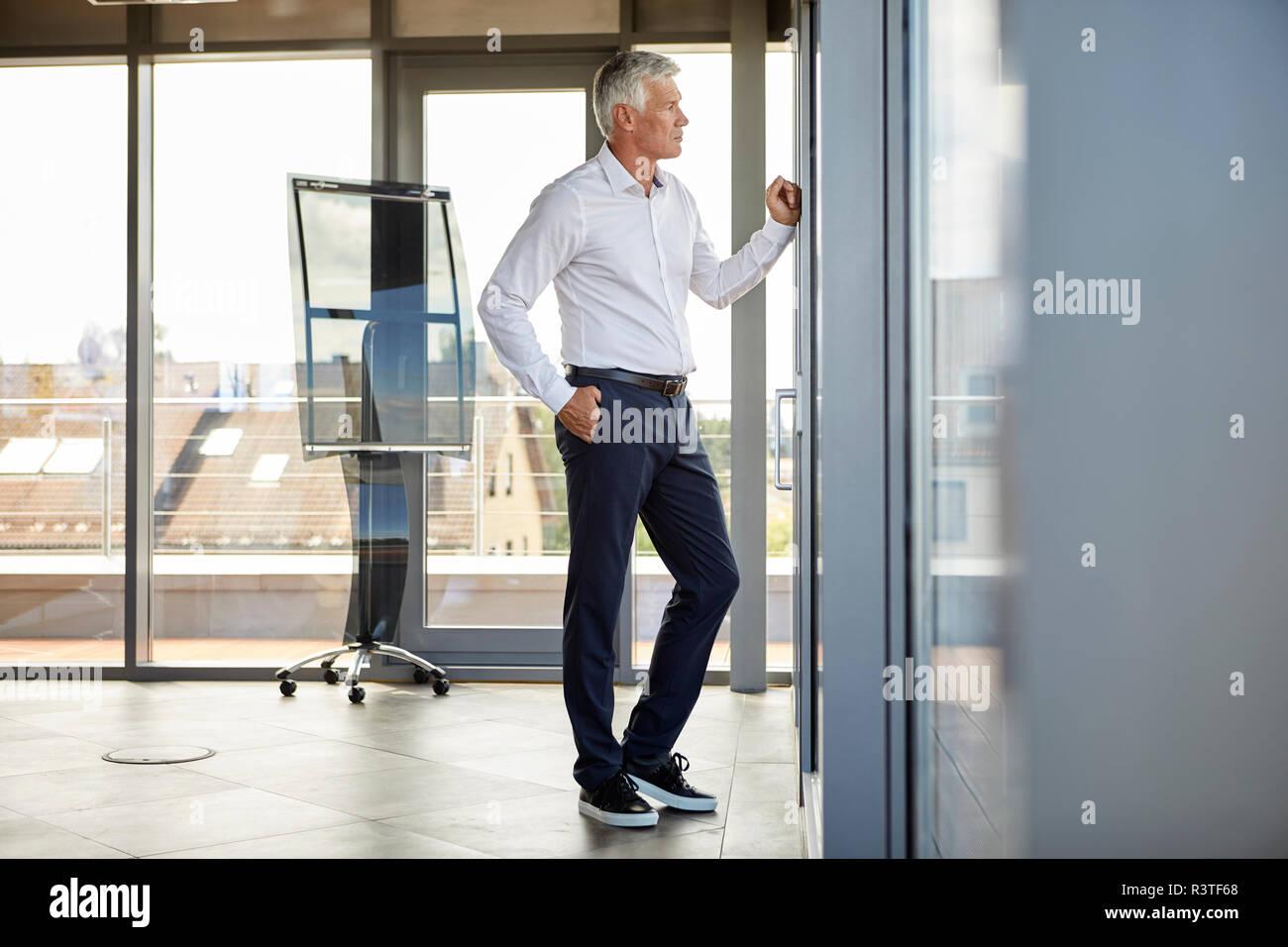 Inquiets businessman standing in office, à la fenêtre de Banque D'Images