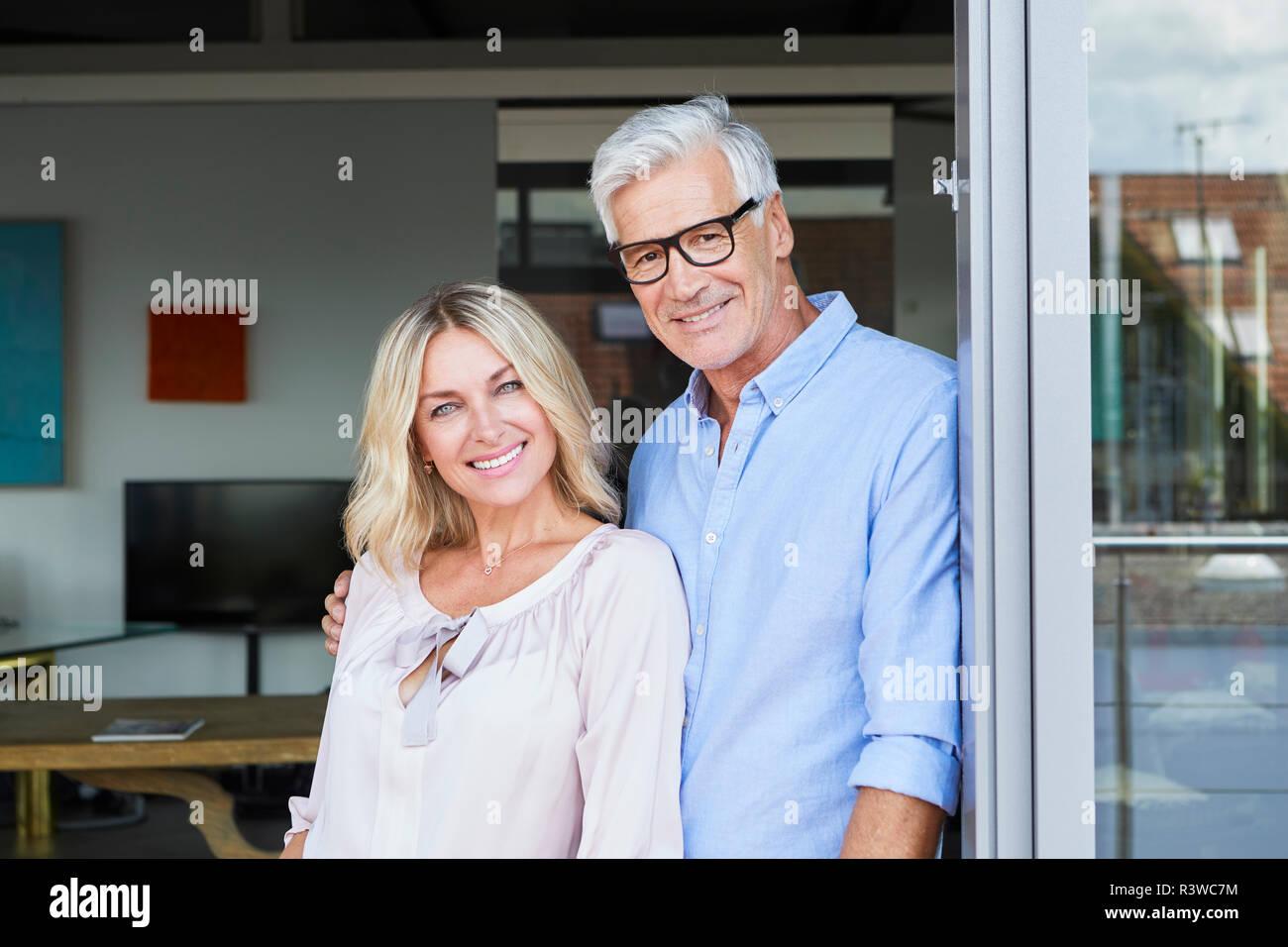 Portrait of smiling mature couple sur le balcon à la maison Banque D'Images