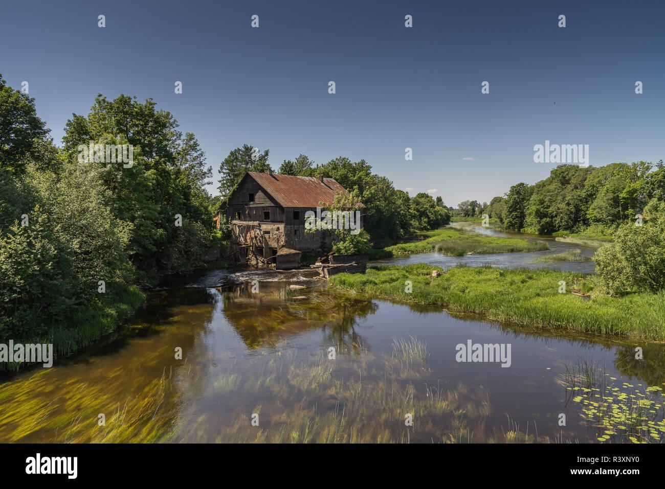 Ancien moulin à eau abandonnés entouré par une nature magnifique. Maison construite en pierre et en bois, murs extérieurs et délabrées bridge sur la rivière est reflecti Banque D'Images