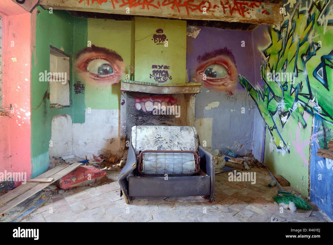 Des murs couverts de graffitis, de détritus éparpillés au sol et canapé cassée dans l'accroupissement Intérieur de maison abandonnée France Photo Stock