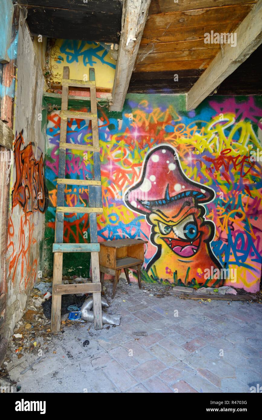 Des murs couverts de graffitis, des échelle branlante & Magic Mushroom design en Squat Intérieur de maison abandonnée France Photo Stock