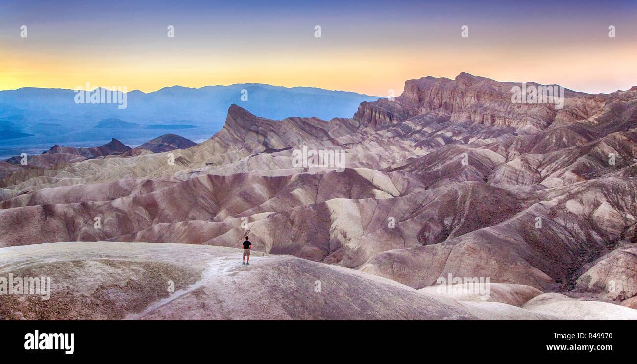 Vue panoramique de l'homme bénéficiant au coucher du soleil célèbre Zabriskie Point dans la belle lumière du soir doré en été, Death Valley National Park, Californie Banque D'Images