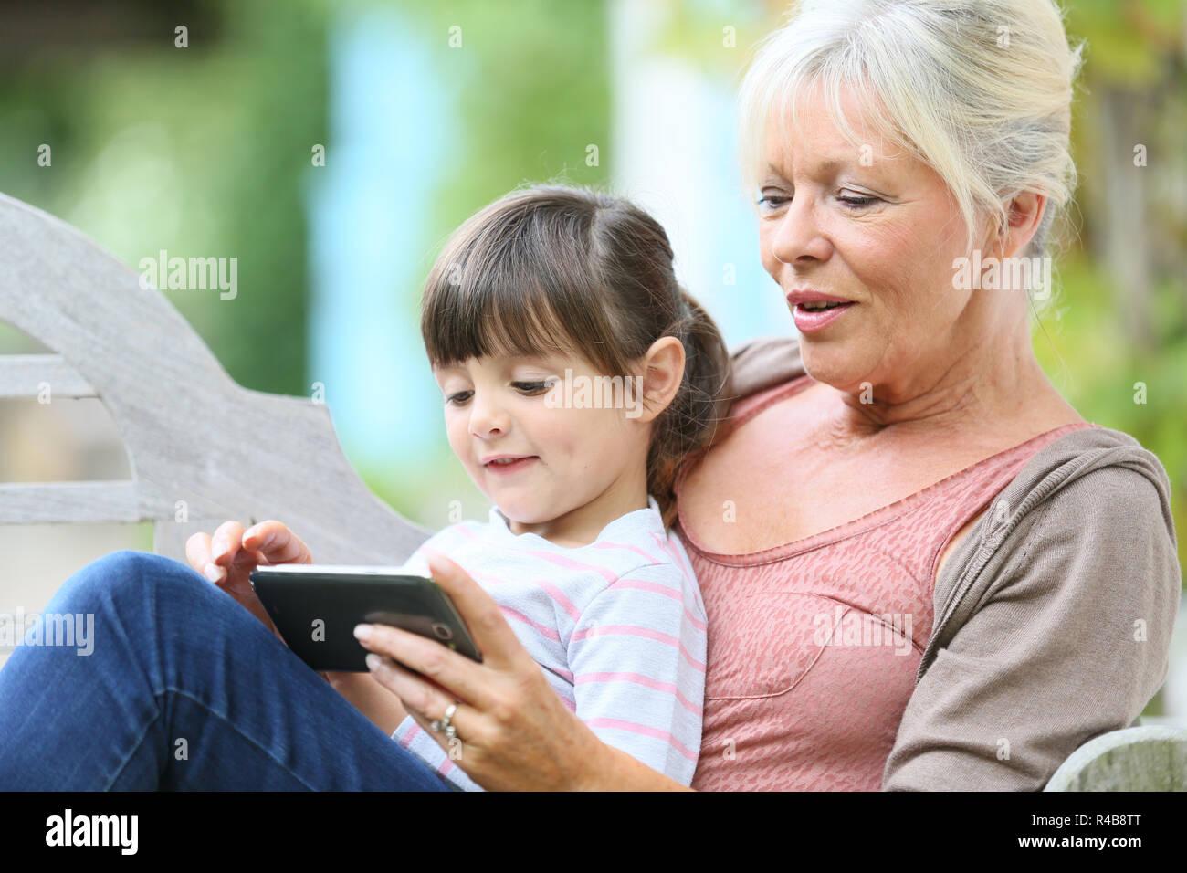 Hauts femme avec jeu de grandkid sur smartphone Photo Stock
