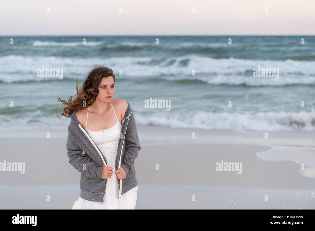 Jeune femme en grelottant de froid, triste pull robe blanche sur la plage  coucher du 4844cf60f7c