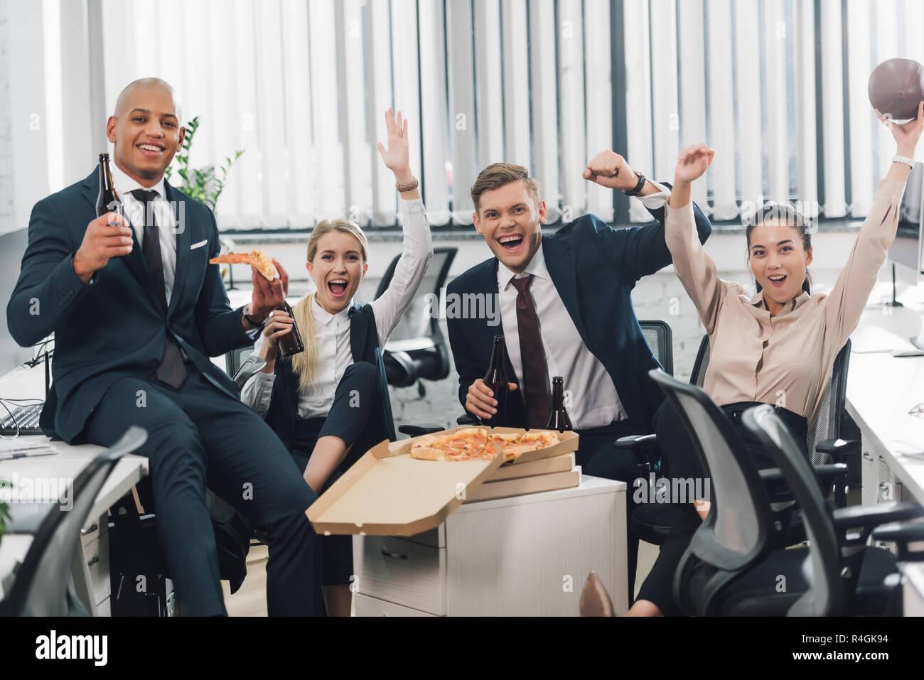 Joyeux jeunes gens d'affaires de boire une bière et manger une pizza in office Banque D'Images