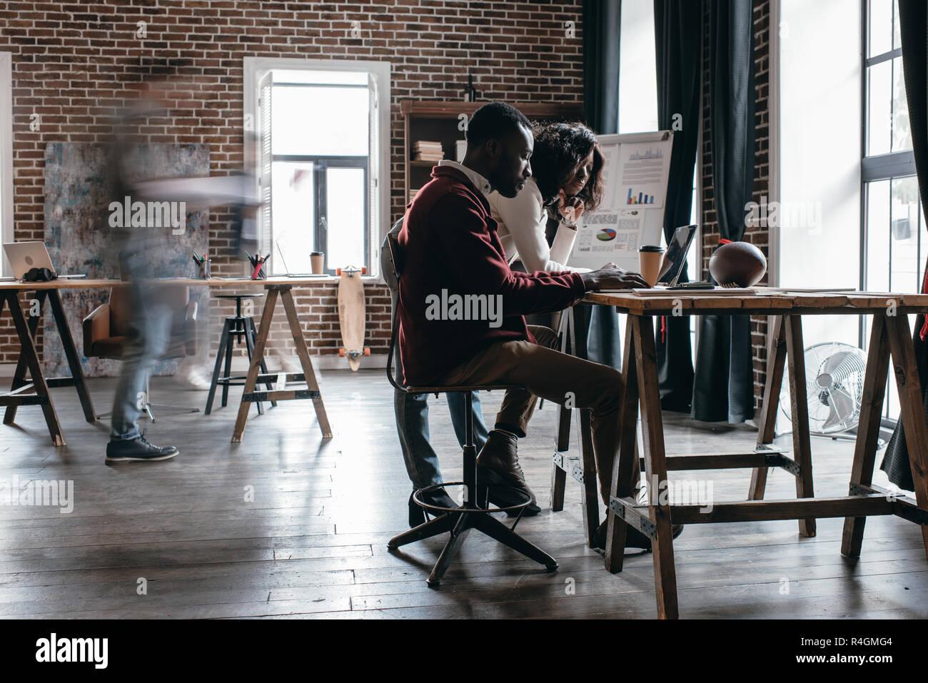 African American couple d'affaires occasionnels travaillant au bureau avec des collègues dans le motion blur en bureau loft moderne Photo Stock