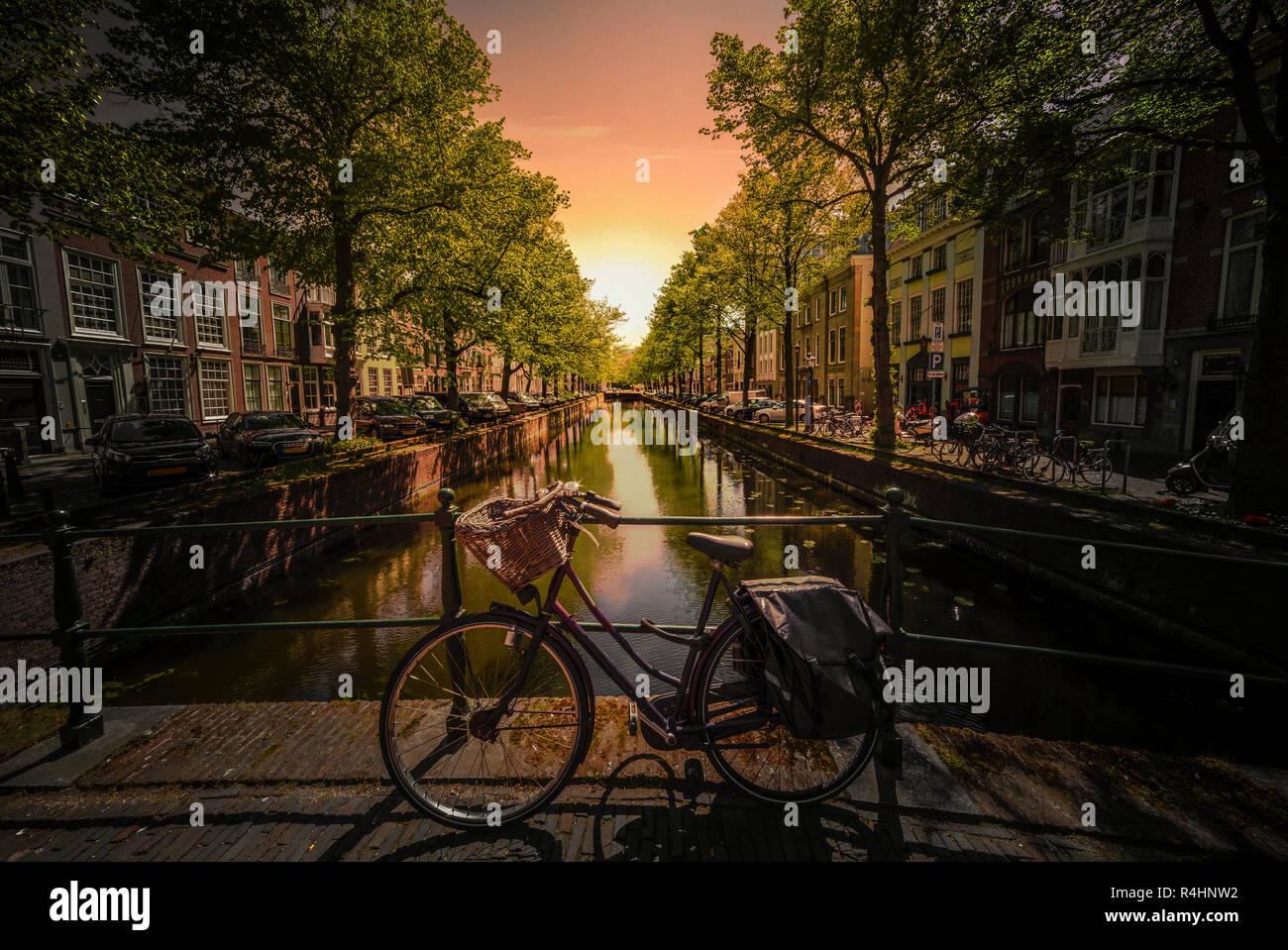 Scène emblématique d'Amsterdam avec le vélo garé sur un pont au-dessus d'un canal d'eau calme, Pays-Bas Banque D'Images