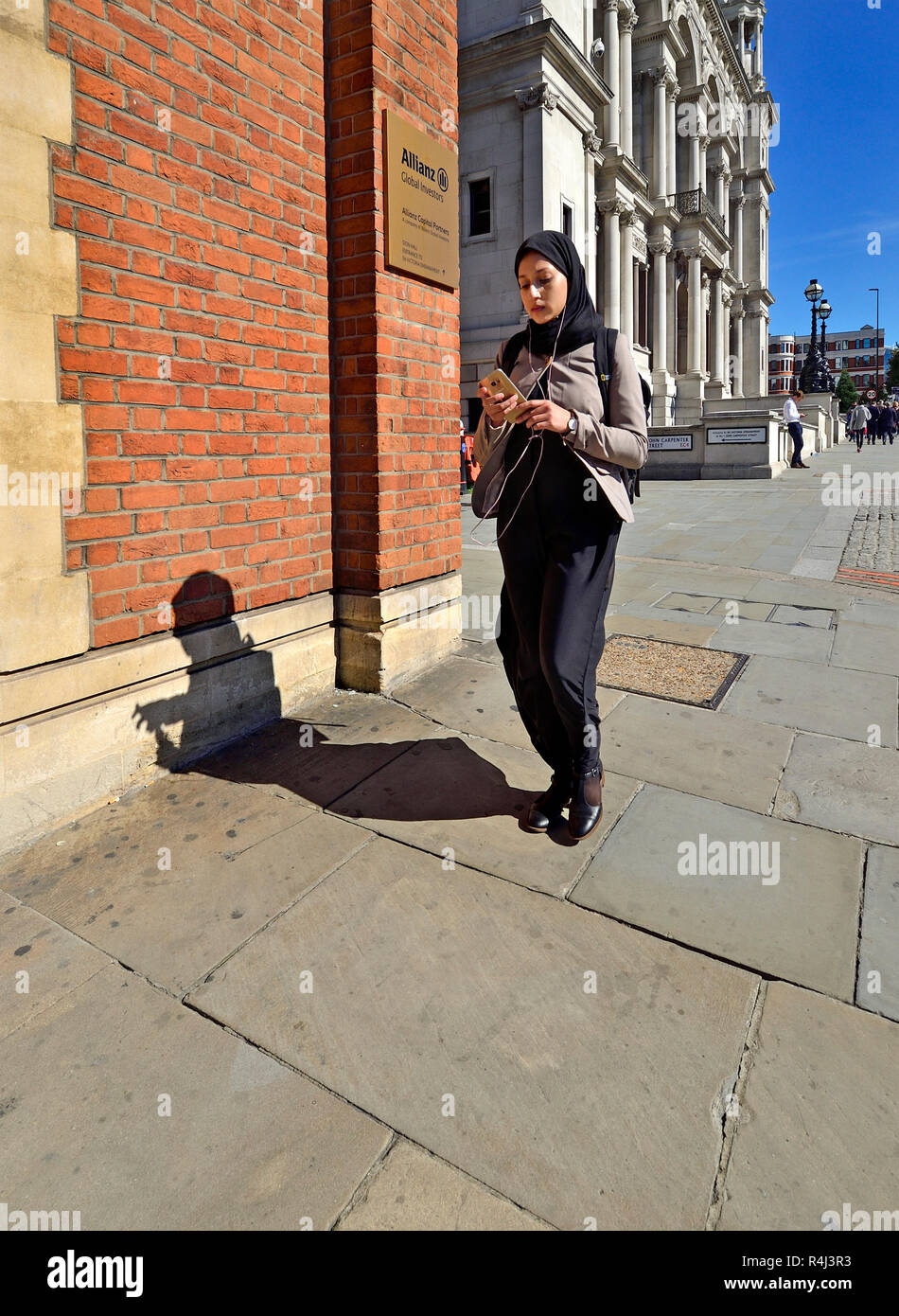fcfb39c37171 Femme dans un foulard en utilisant son téléphone mobile, le centre de  Londres, Angleterre