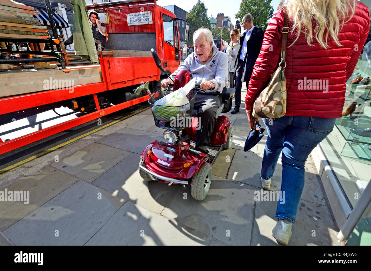 Homme conduisant un scooter de mobilité sur la chaussée dans le centre de Londres, Angleterre, Royaume-Uni. Photo Stock