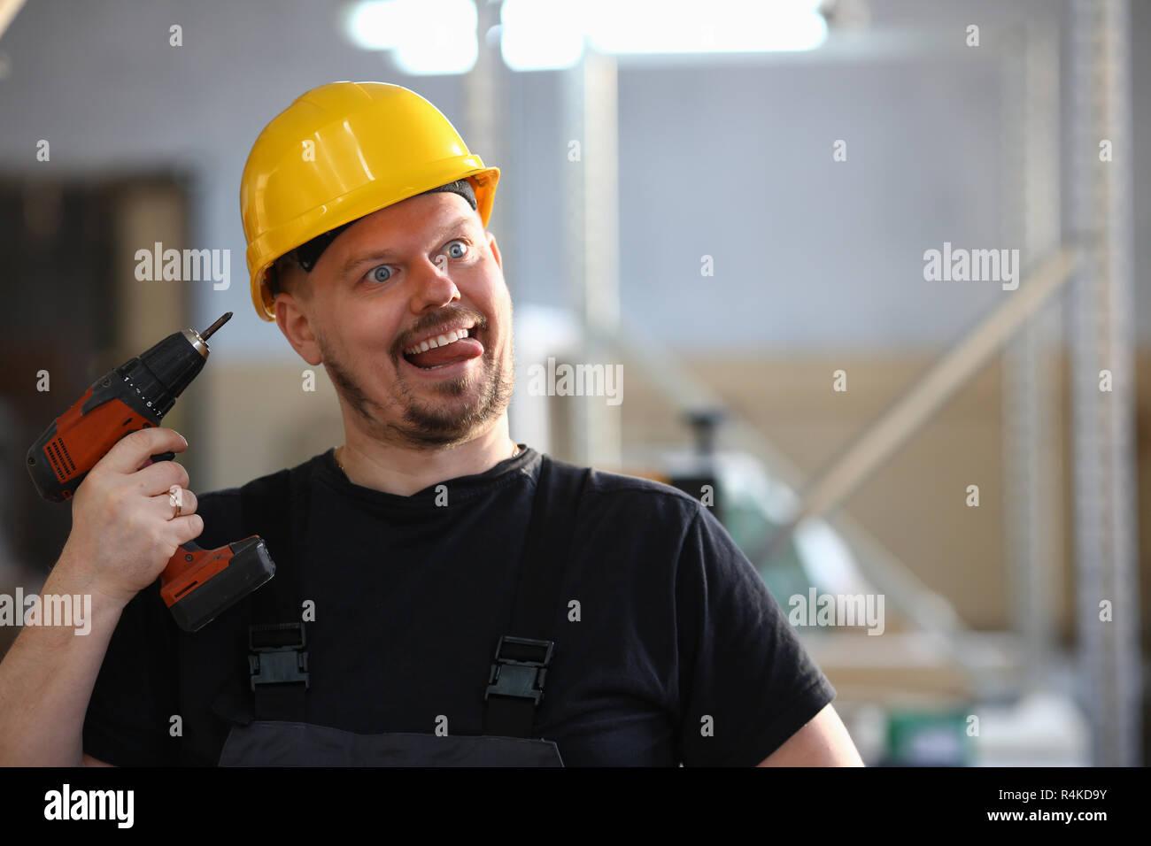 Travailleur à l'aide de la perceuse électrique idiot portrait Photo Stock
