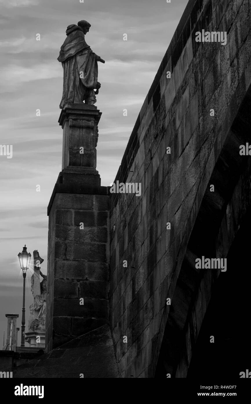 Statue baroque de Saint Nicolas de Tolentino situé sur le pont Charles à Prague, prises d'un angle de vue et une faible lumière sur la rue Banque D'Images
