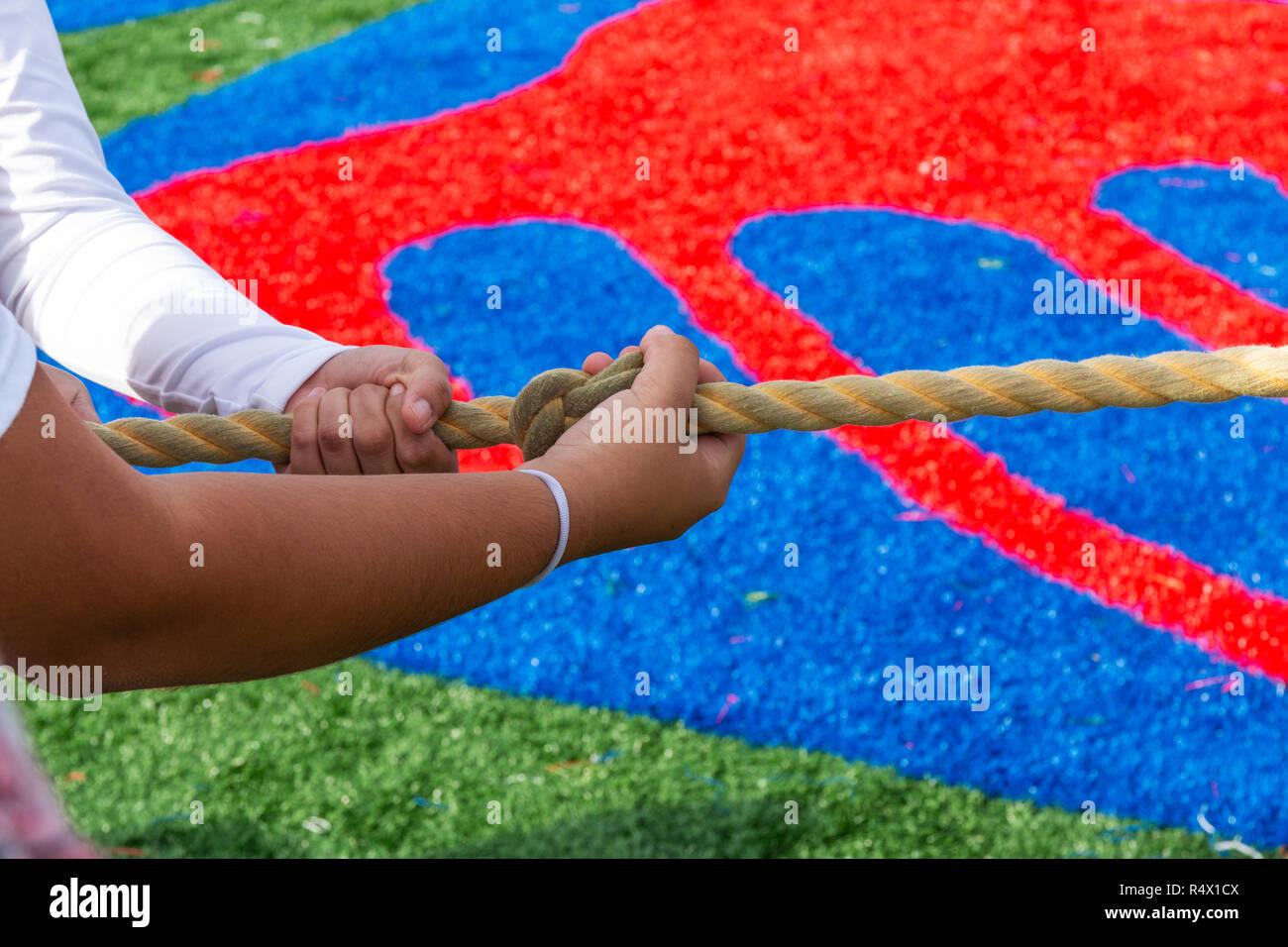 Mains agrippant le noeud dans la corde au cours d'un remorqueur de la guerre jeu sur un terrain de gazon. Photo Stock