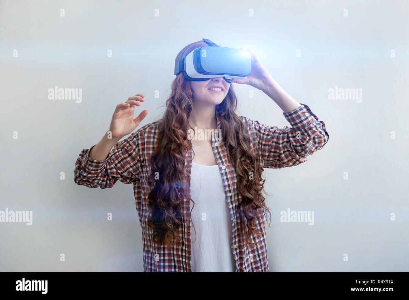 Sourire jeune femme portant à l'aide de lunettes de réalité virtuelle VR casque casque sur fond blanc. Avec l'aide de lunettes de réalité virtuelle. La technologie, simulation, hi-tech, concept de jeu vidéo Banque D'Images