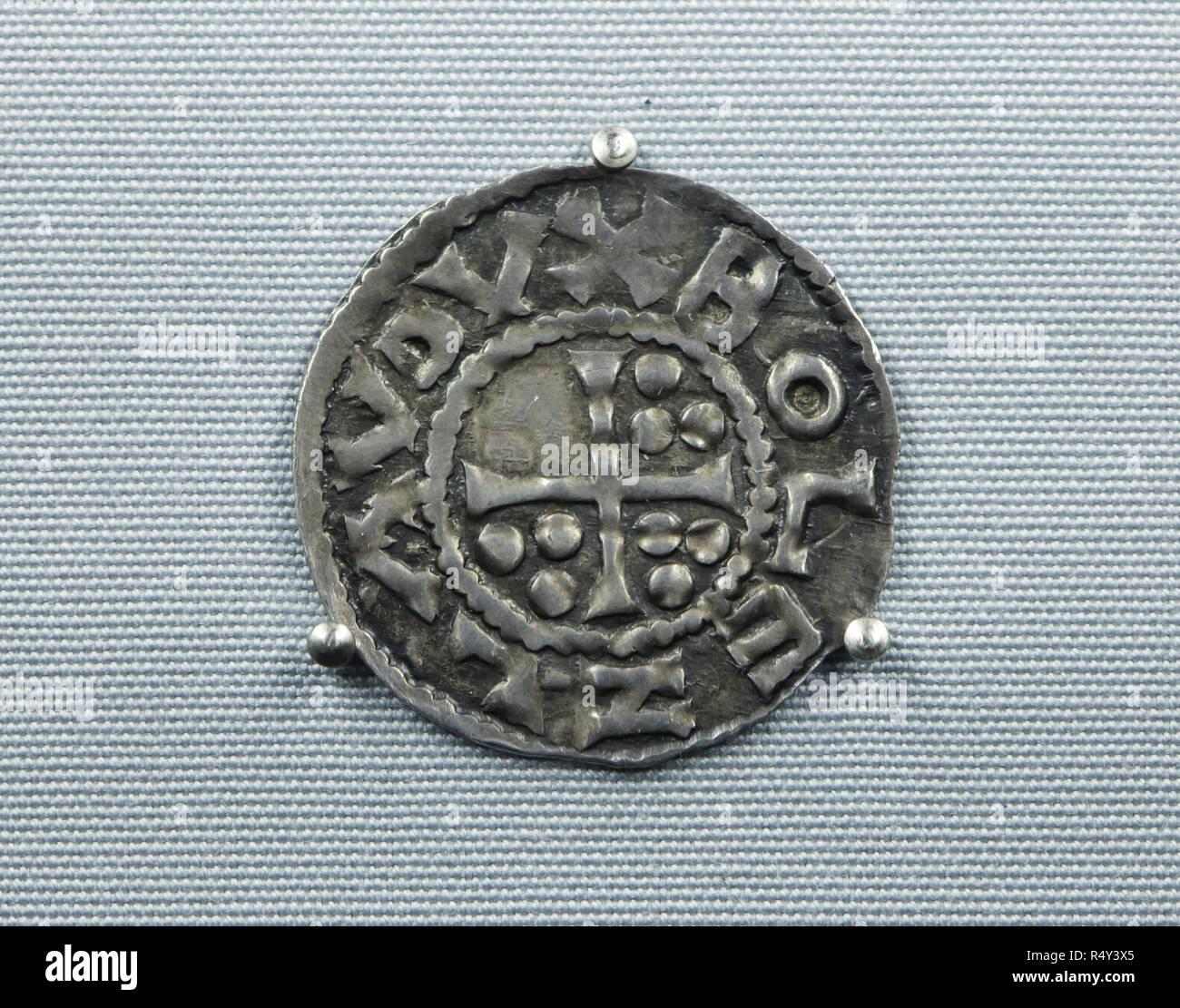 La plus ancienne pièce de monnaie tchèque en date du 10e siècle sur l'affichage à l'anniversaire d'exposition dans le Musée National (Národní muzeum) à Prague, République tchèque. La pièce d'argent de Bohême médiévale (denier) frappées à Prague sous le règne du Duc Boleslas I le cruel avant de 966 est considéré comme la plus ancienne pièce de monnaie frappées en territoire qui est maintenant la République tchèque. Une croix avec neuf adore est représenté dans le coin avec une inscription autour de 'BOLEZLAV DVX' ('Duke Boleslas'). L'exposition consacrée à l'occasion du 200e anniversaire du Musée national présente 200 des plus importants points de Photo Stock