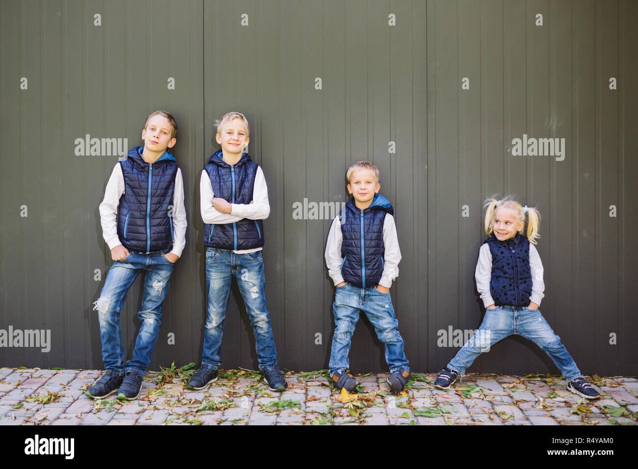 Funny Portrait grande famille de trois frères et sœur posant debout sur fond de croissance de mur en pleine croissance. Tout aussi élégamment vêtus de gilets et bleu jeans. Thème fille en cercle masculin Banque D'Images