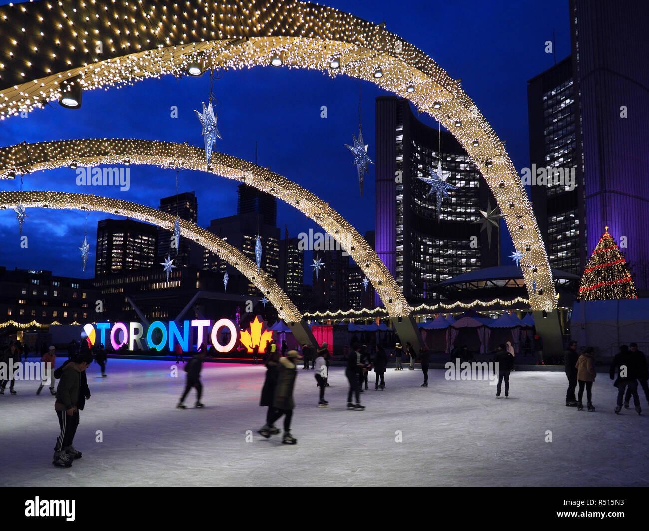 Patinoire avec des lumières de Noël et allumé Toronto signe, soir devant l'Hôtel de ville moderne de Toronto. Photo Stock