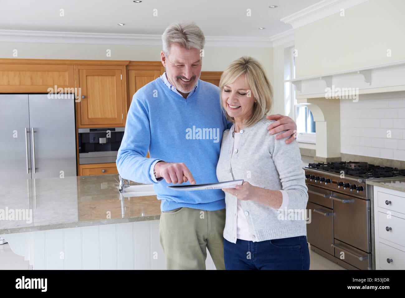 Affichage Nouveau Couple debout dans la cuisine à domicile à Brochure Photo Stock