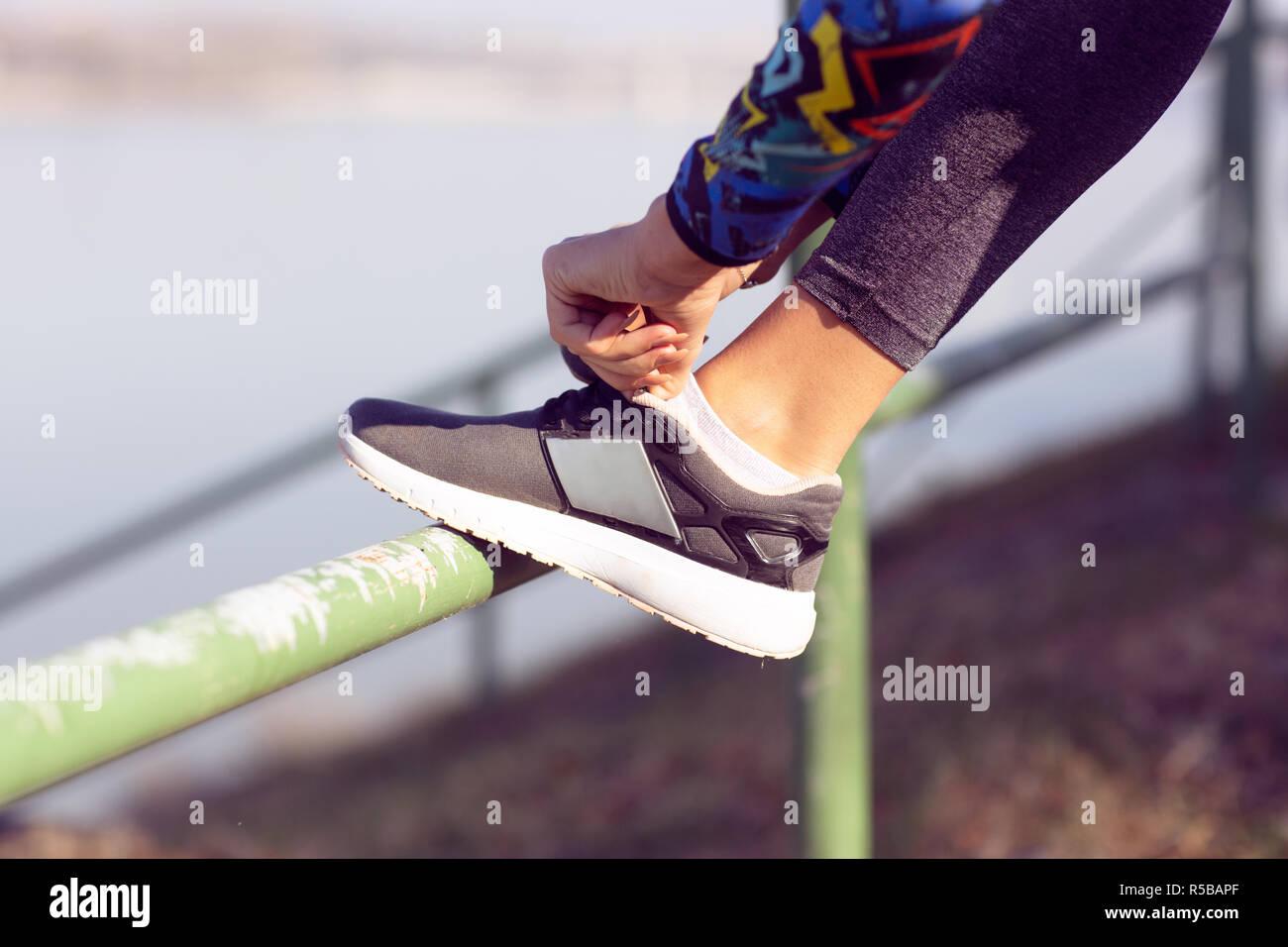 Attacher la chaussure de sport. Une jeune athlète se préparer pour l'athlétisme et la formation de remise en forme en plein air. Sport, exercice, fitness, entraînement. Mode de vie sain Photo Stock
