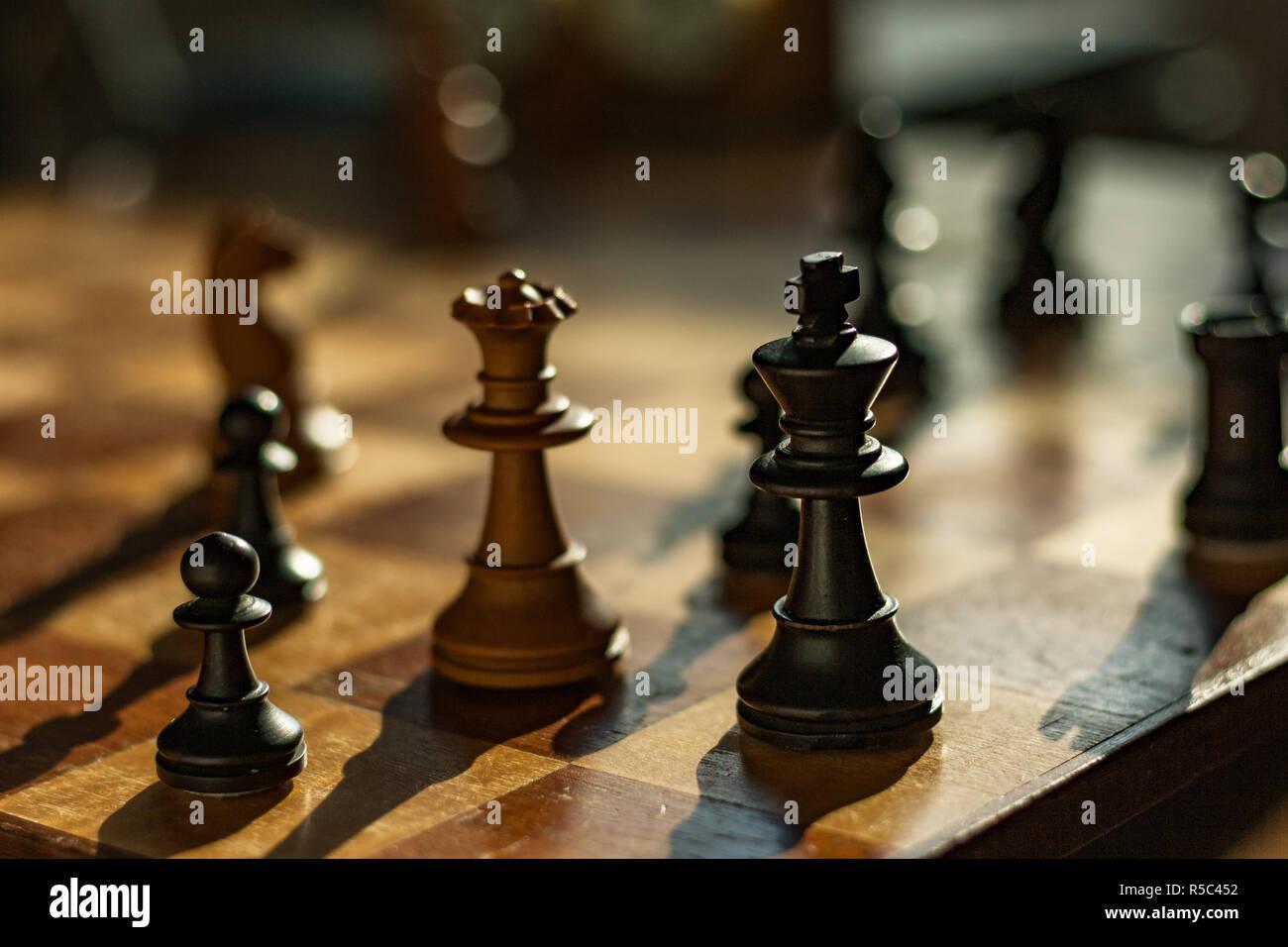 Reine et Roi: pièces d'échecs sur un conseil. La Reine blanche mates le roi noir dans un jeu d'échecs. Banque D'Images