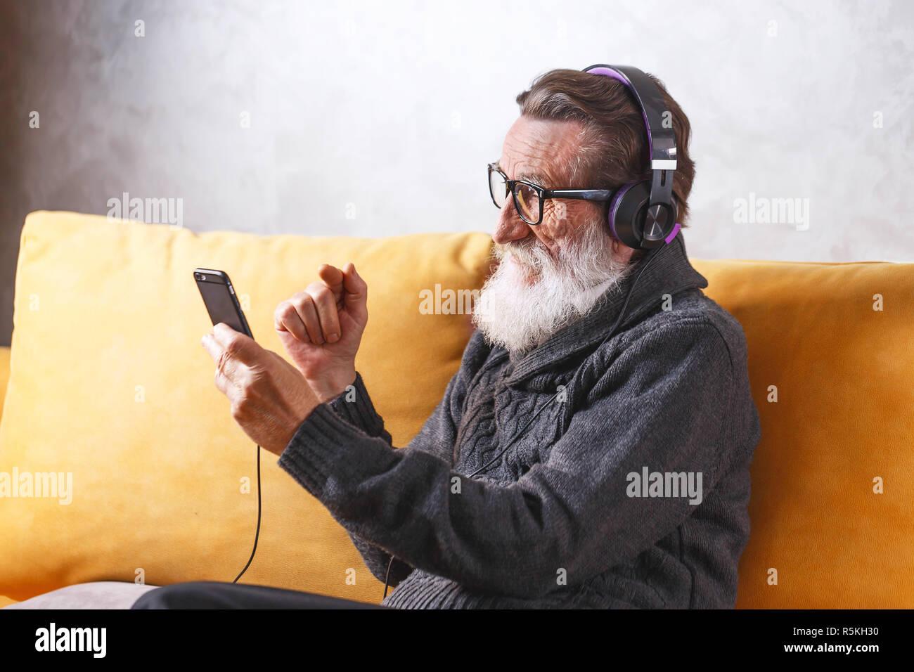 Joyeux Senior homme barbu portant des lunettes en pull gris smartphone à l'aide tout en restant assis dans le casque sur un canapé jaune dans sa lumière, salon de la technologie moderne, communication concept Banque D'Images