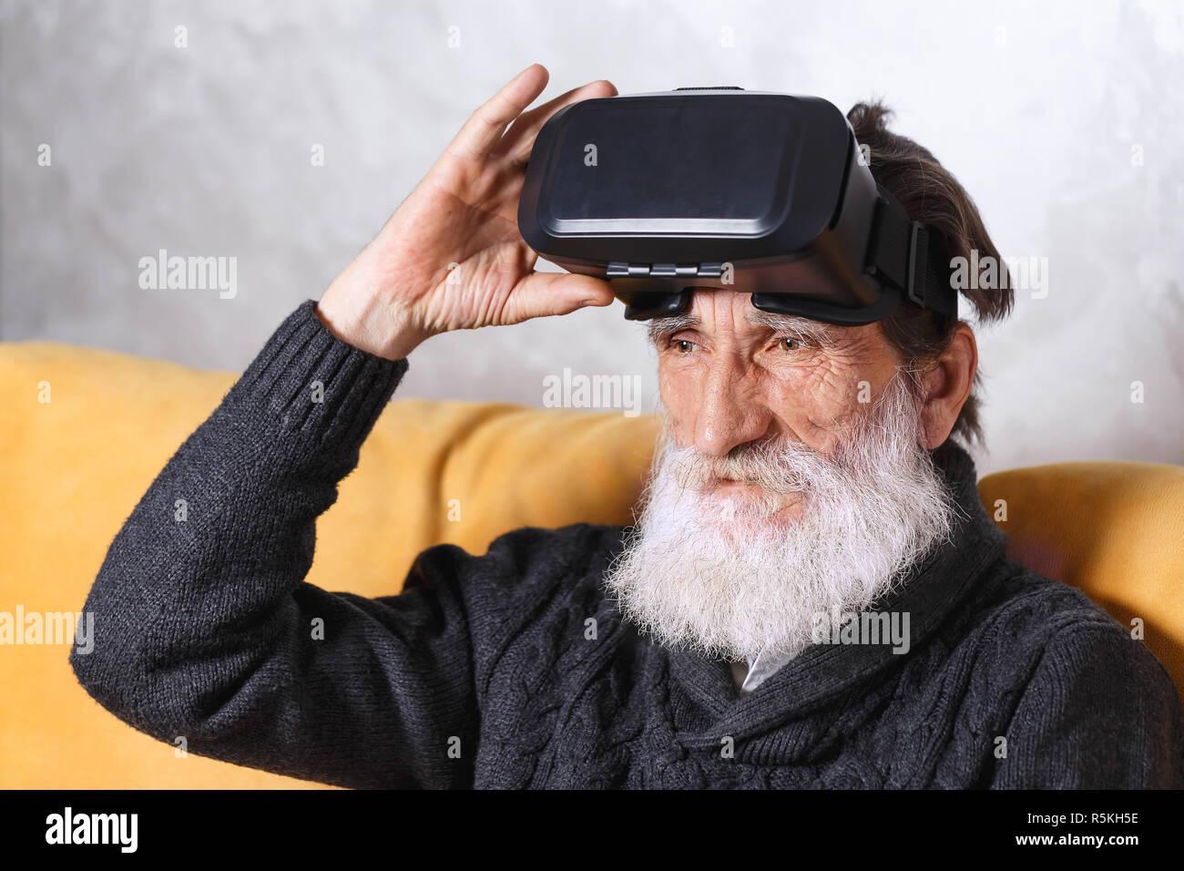 Homme barbu senior contemporain en pull gris assis dans VR sur le canapé jaune lunettes dans le salon lumineux, avenir technologie concept Banque D'Images