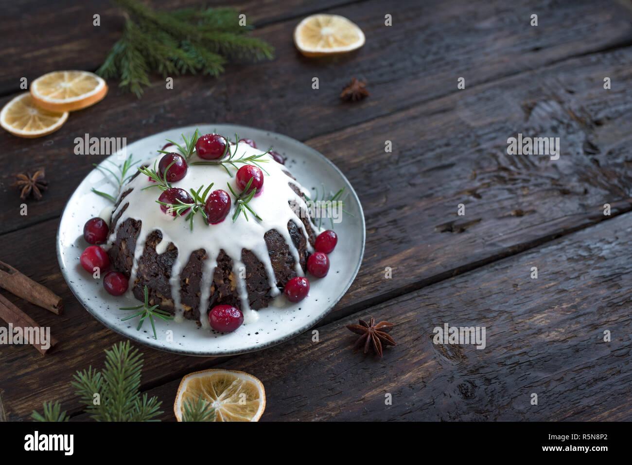 Le pudding de Noël, fruits gâteau décoré avec du glaçage et des canneberges sur table en bois rustique, de copier l'espace, vue d'en haut. Noël traditionnel fait maison desser Photo Stock
