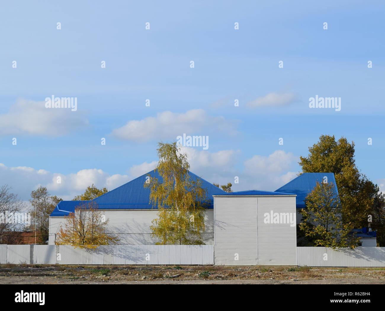 L'immeuble avec garage et bleu métal-plastique en toiture en tôle ondulée. Banque D'Images