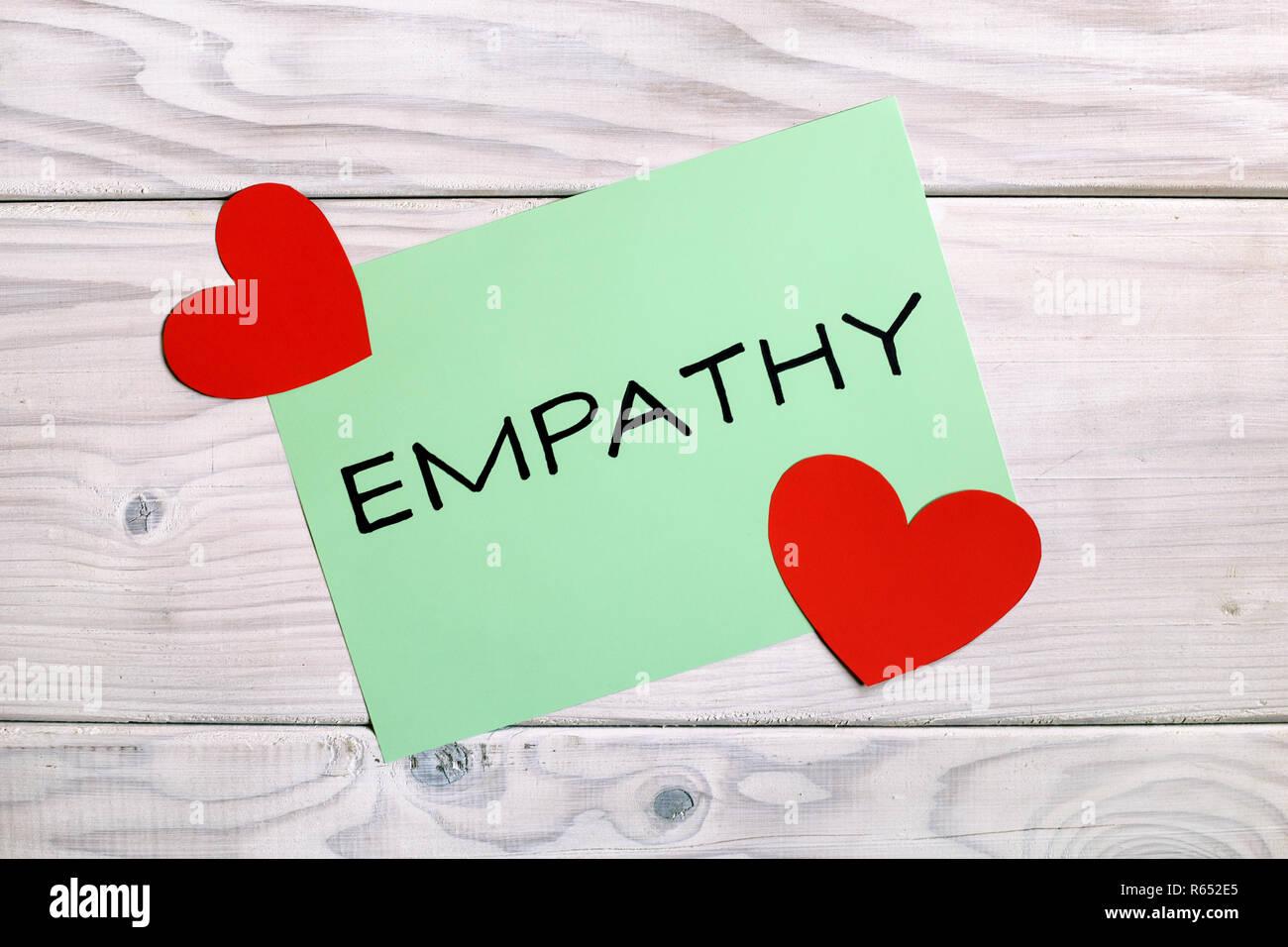 Mot d'empathie et de coeur des formes sur table en bois. Photo Stock