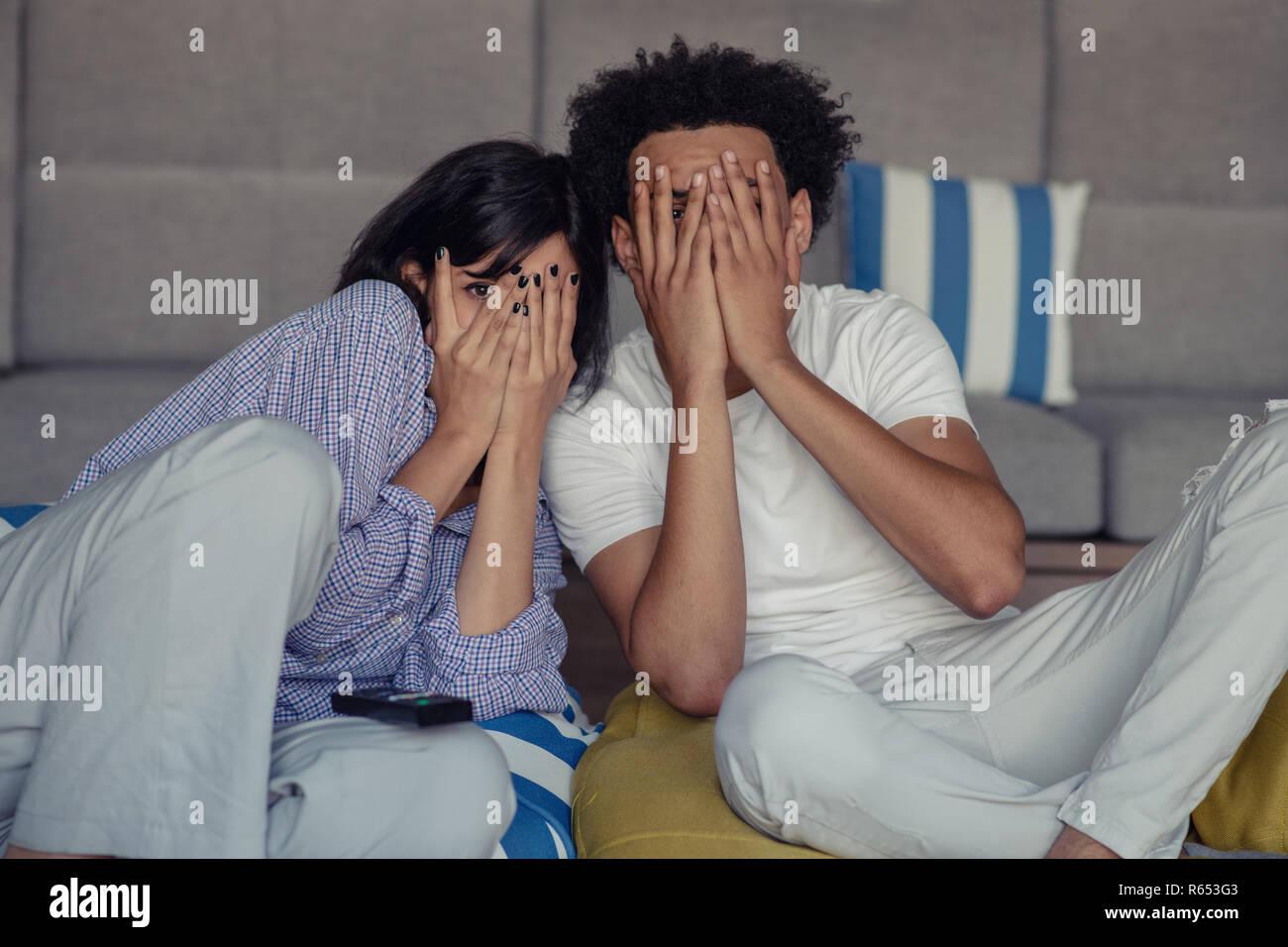 Jeune couple à la maison à regarder un film avec pop-corn Photo Stock