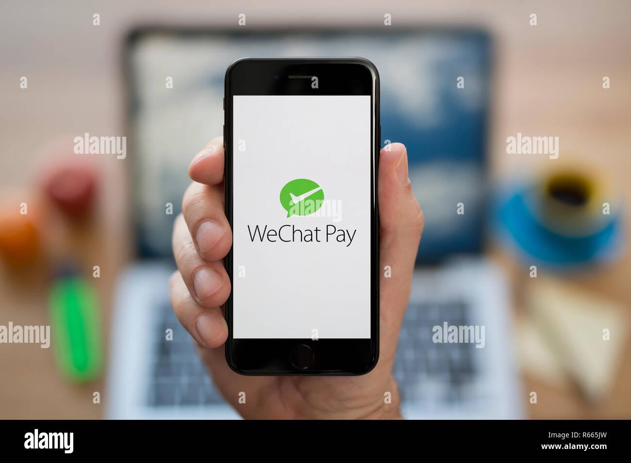 Un homme se penche sur son iPhone qui affiche le logo de WeChat payer, alors qu'assis à son bureau de l'ordinateur (usage éditorial uniquement). Photo Stock