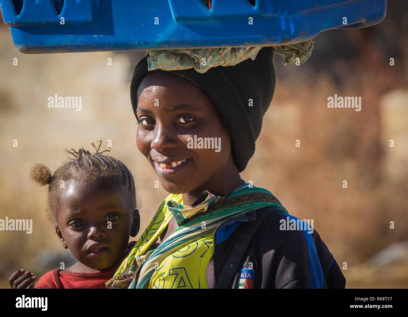 Jeune femme portant son épicerie sur sa tête sur le marché, dans la province de Huila, Hoque, Angola Photo Stock