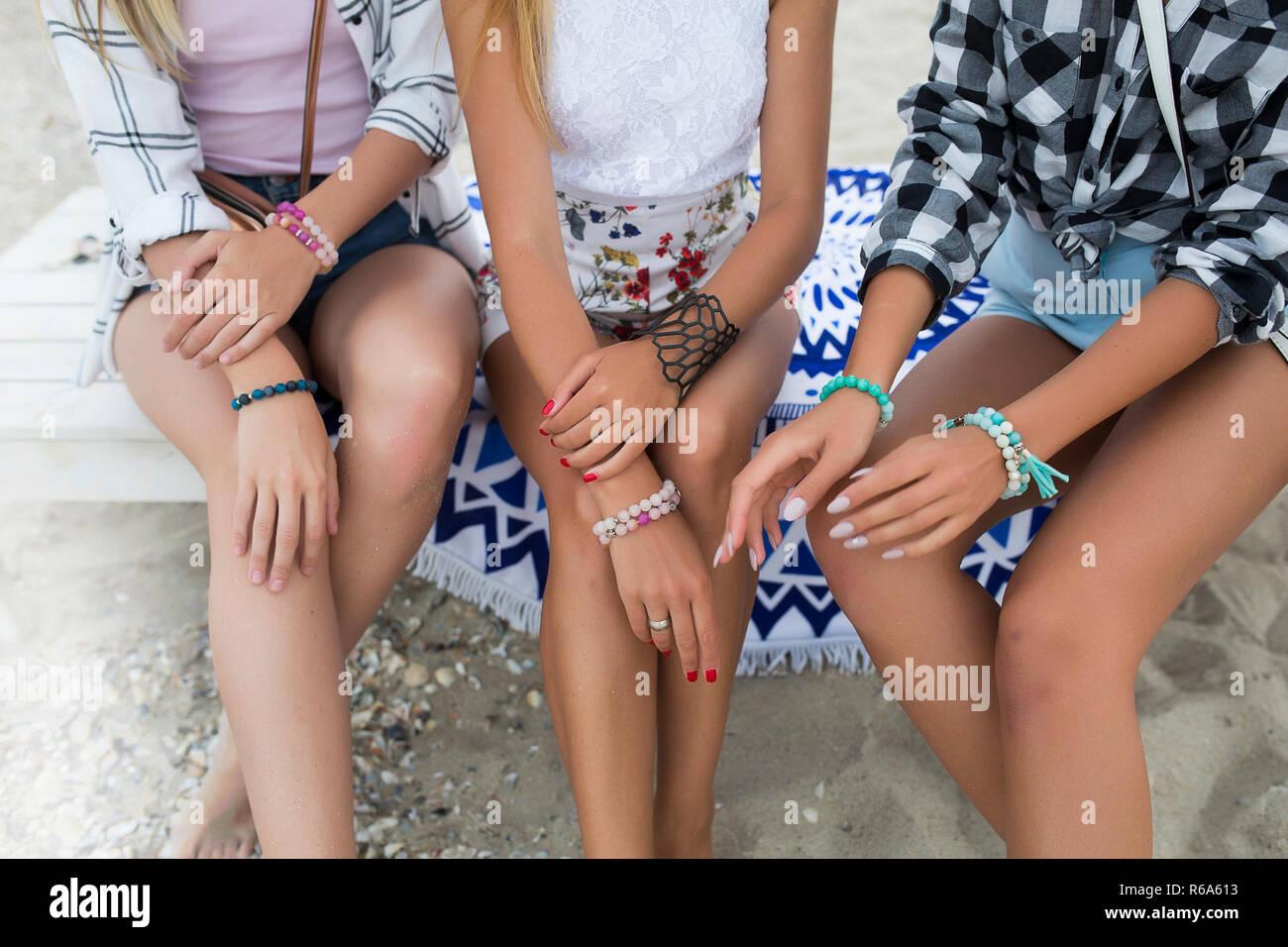Tir d'été sur la plage, trois jeunes filles en shorts et blouses avec la peau bronze bronzé assis sur le banc recouvert d'une couverture.sur beau Photo Stock
