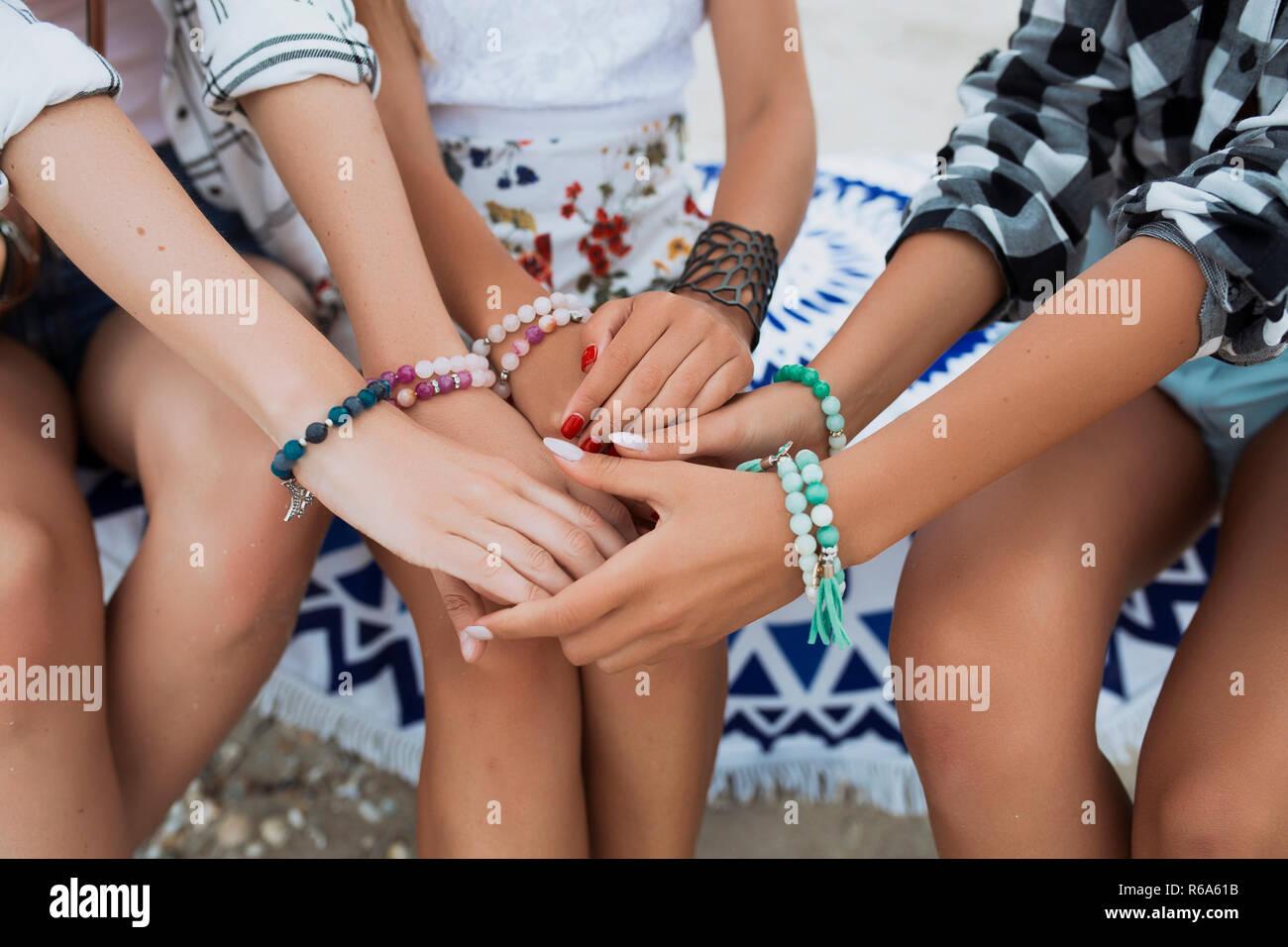 Photo en gros plan des mains avec différents bracelets lumineux et accessoires. Main dans la main ensemble, l'amitié et l'amour. Tir d'été Photo Stock