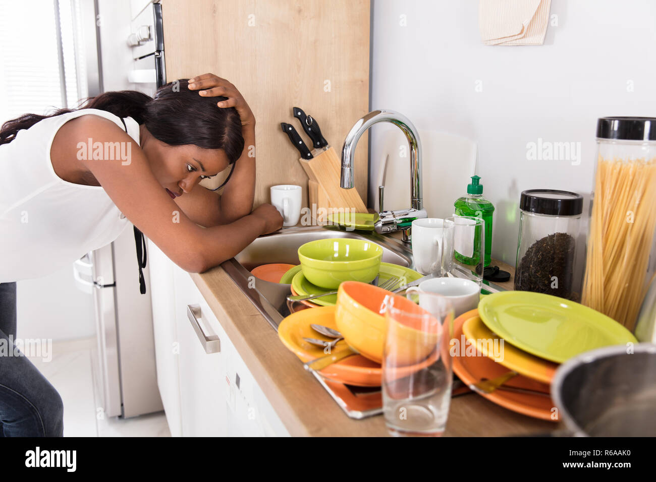 Souligné Woman Leaning près de l'évier de cuisine à la recherche d'ustensiles à Banque D'Images