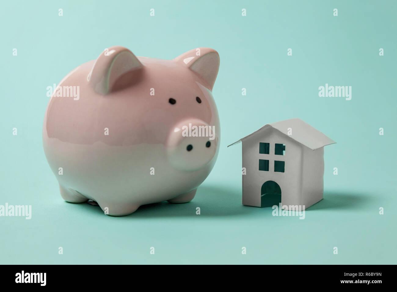 Conception simple avec miniature toy house, tirelire isolé isolé sur fond bleu pastel très tendance aux couleurs vives. L'assurance des biens hypothécaires dream home banking concept prêt à l'investissement. Copy space Banque D'Images