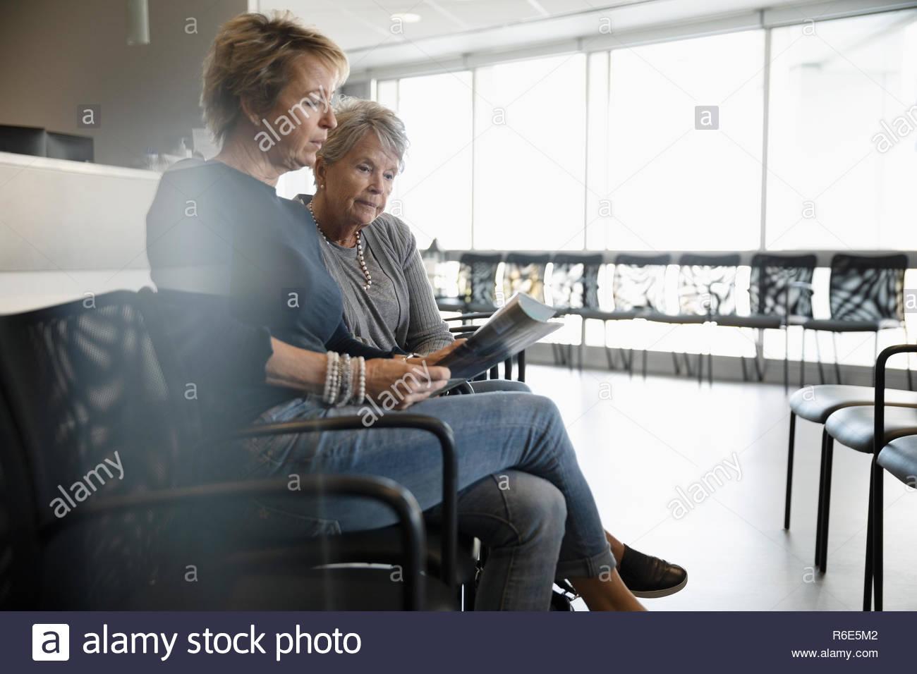 La lecture de la brochure fille mère senior en salle d'attente de la clinique Photo Stock