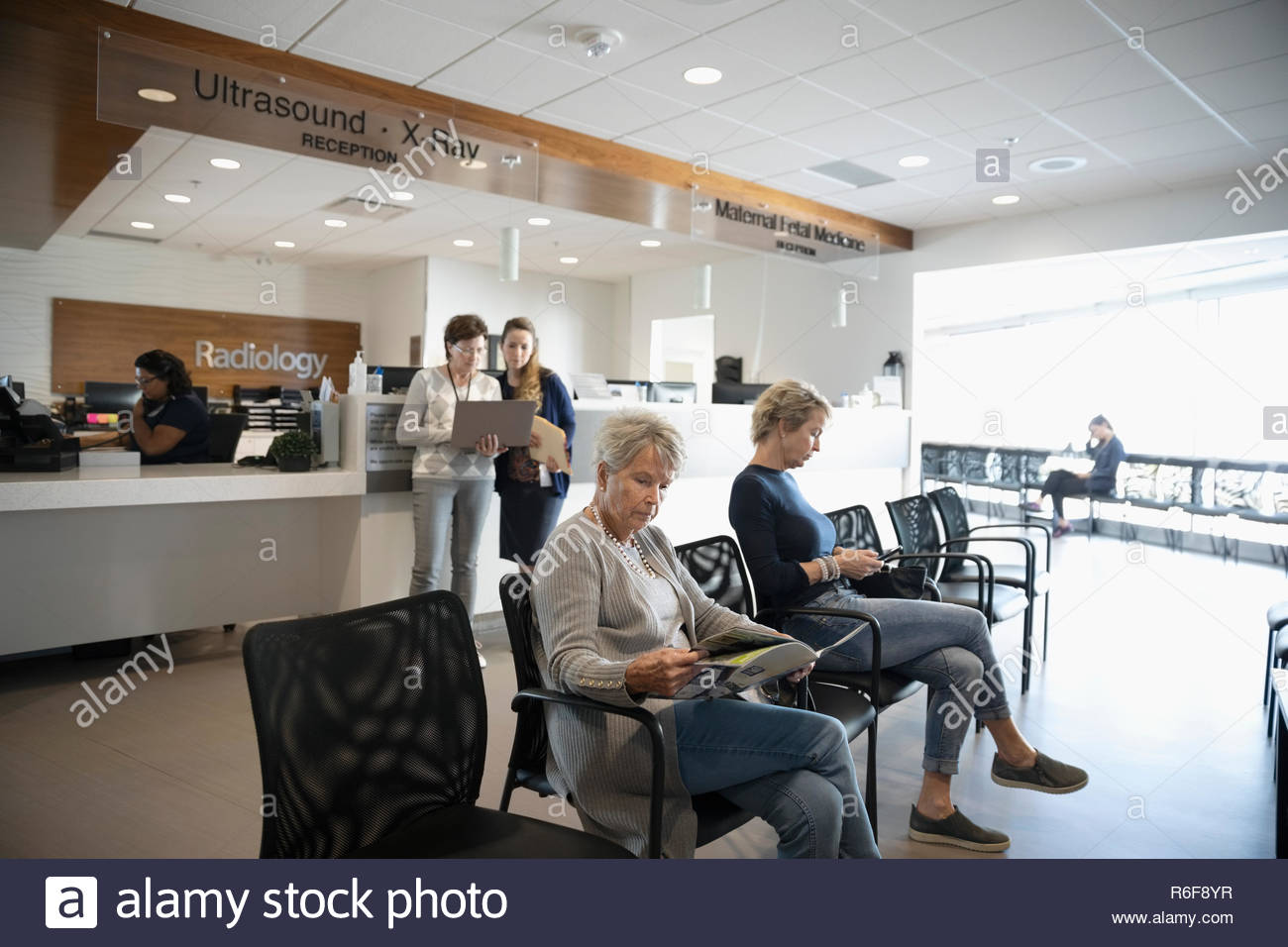 Senior woman reading brochure, l'attente dans la salle d'attente de la clinique Photo Stock