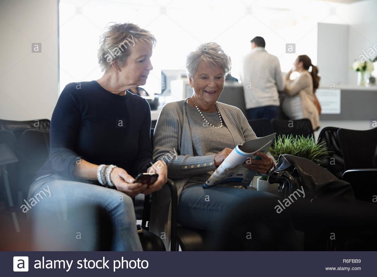 Senior woman reading magazine et de sa fille, l'attente dans la salle d'attente de la clinique Photo Stock