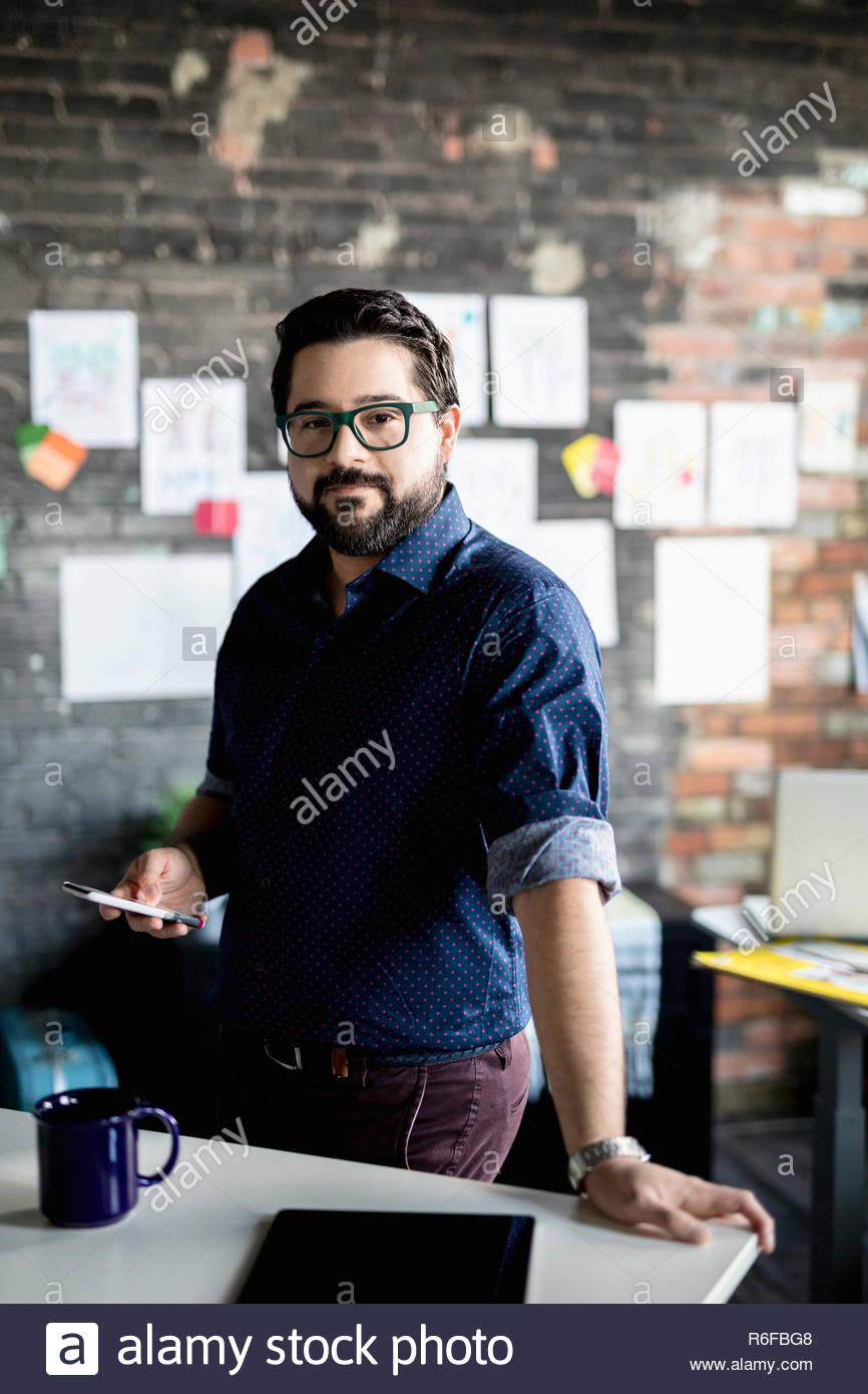 Creative businessman Portrait confiant avec smart phone in office Banque D'Images