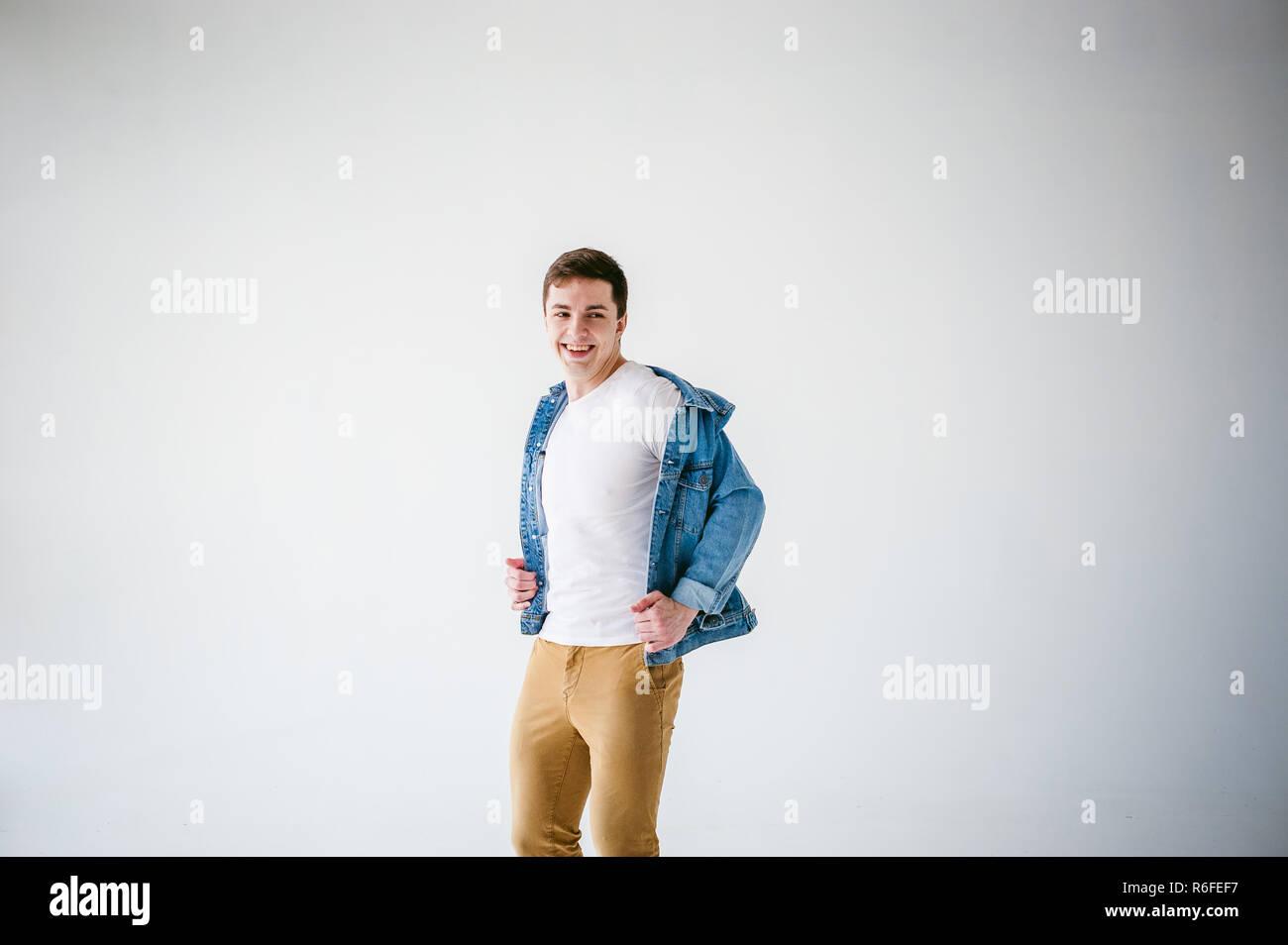 3e8b7f88c41 beau-jeune-homme-de-corps-du-sportif-habille-en-veste-bleu-jeans-dans-le -style-de-la-vieille-ecole-et-t-shirt-blanc-avec-un-pantalon-brun-posant-sur-fond-  ...
