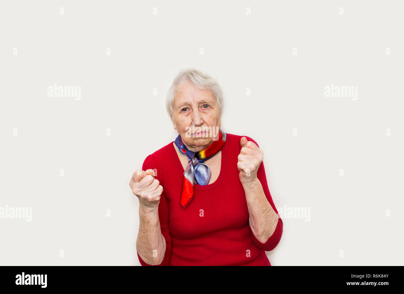 Angry old woman making fists sur fond blanc Banque D'Images