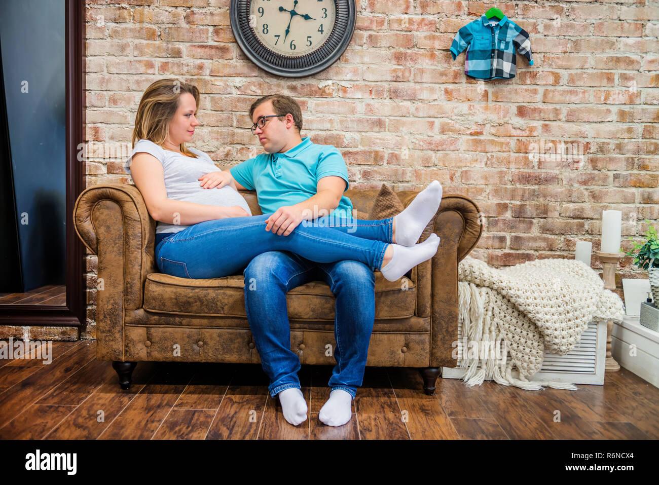 Belle femme enceinte et l homme assis près de wall Photo Stock cfa88d585de