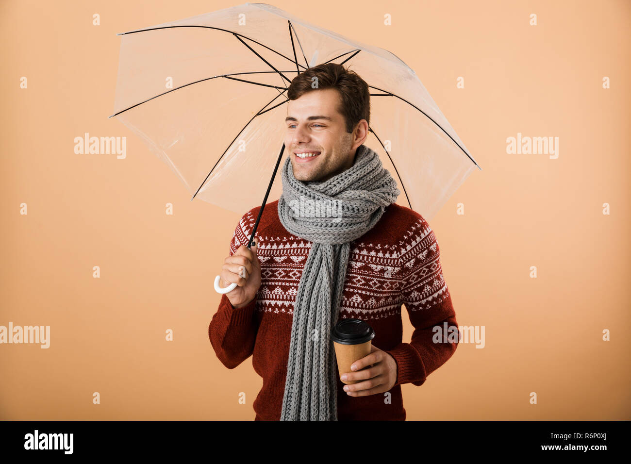cd1c7b99d895 Portrait d un jeune homme habillé en satisfait chandail et isolé sur fond  beige écharpe, debout sous un parapluie, holding Coffee cup