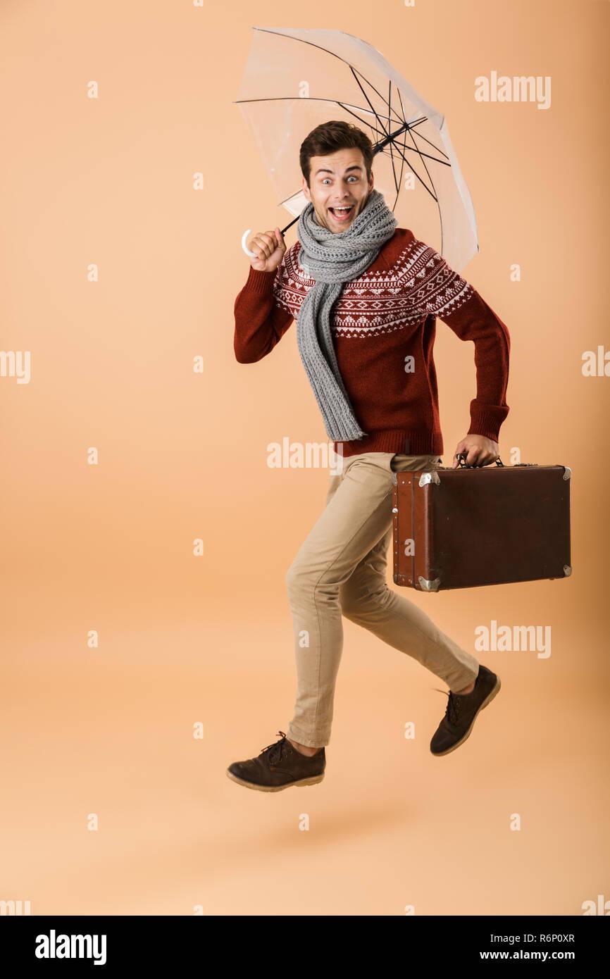d1c77a406f6f Portrait d un jeune homme habillé en chandail et isolé sur fond beige  écharpe,