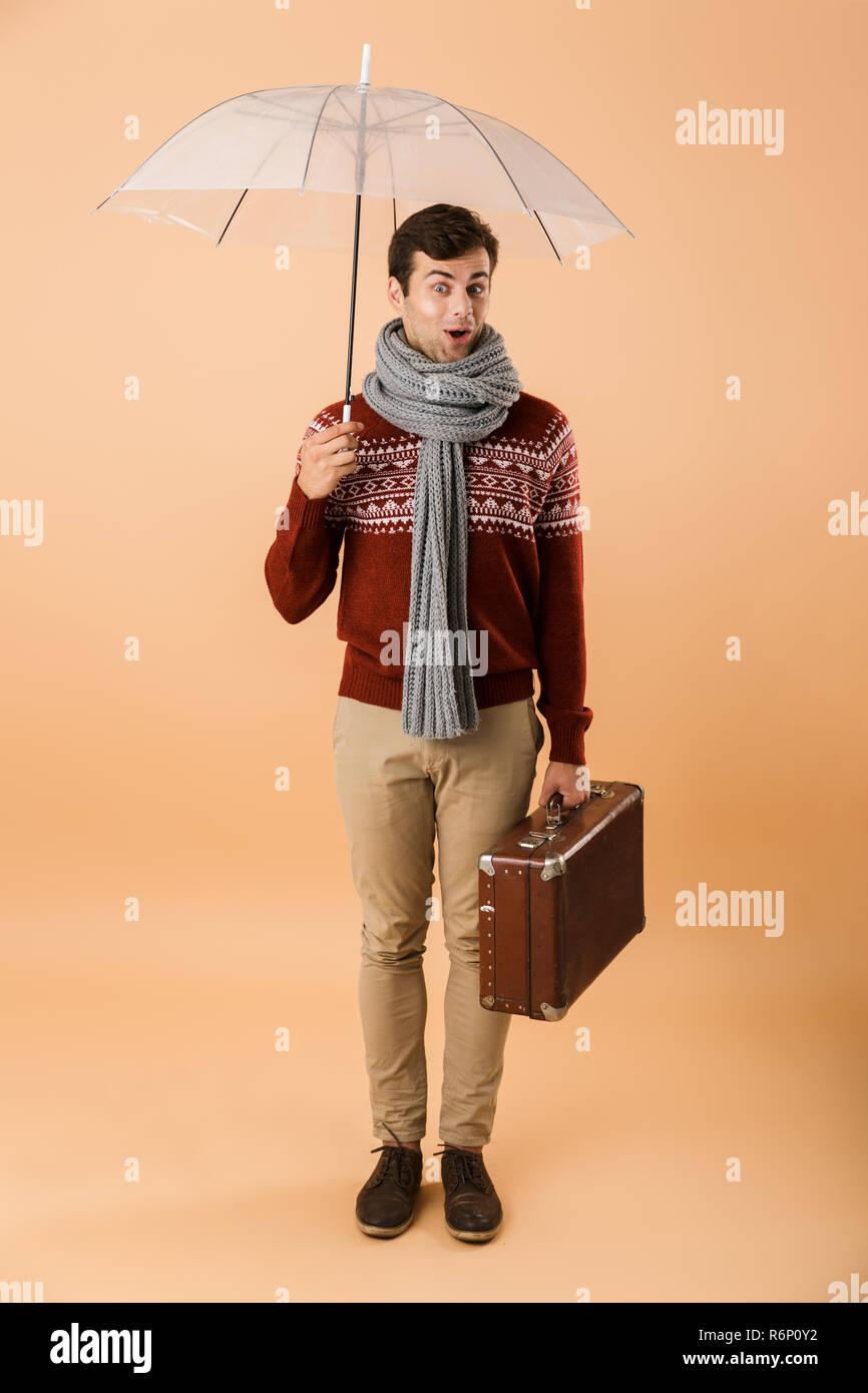 309af615f62e Portrait d un jeune homme excité habillé en chandail et isolé sur fond  beige écharpe
