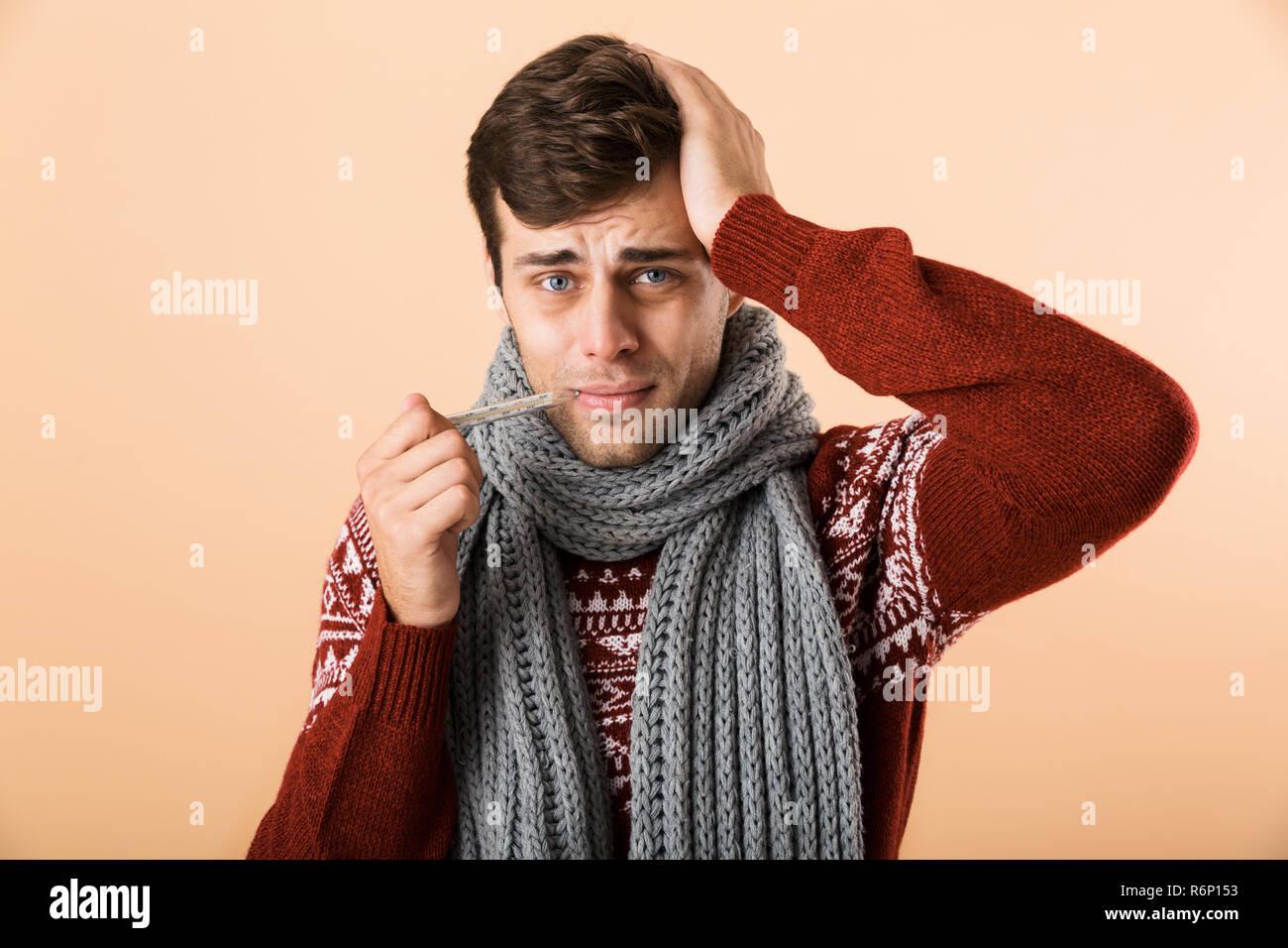 ba804246d7cd Portrait d un jeune homme malade habillé en chandail et isolé sur fond  beige écharpe