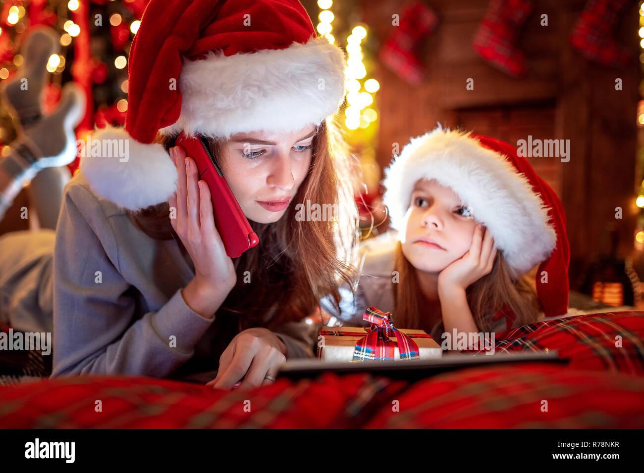 699fa3080ccba Temps de Noël.La famille de la mère et sa fille au père Noël chapeaux et  pyjamas ...