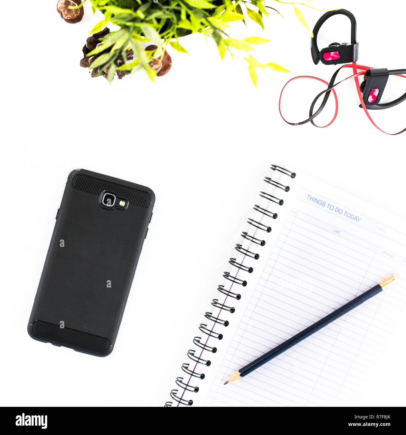 Maquette de téléphone cellulaire sur fond blanc avec des écouteurs, bloc- notes et crayon 0ef4bc0a928d