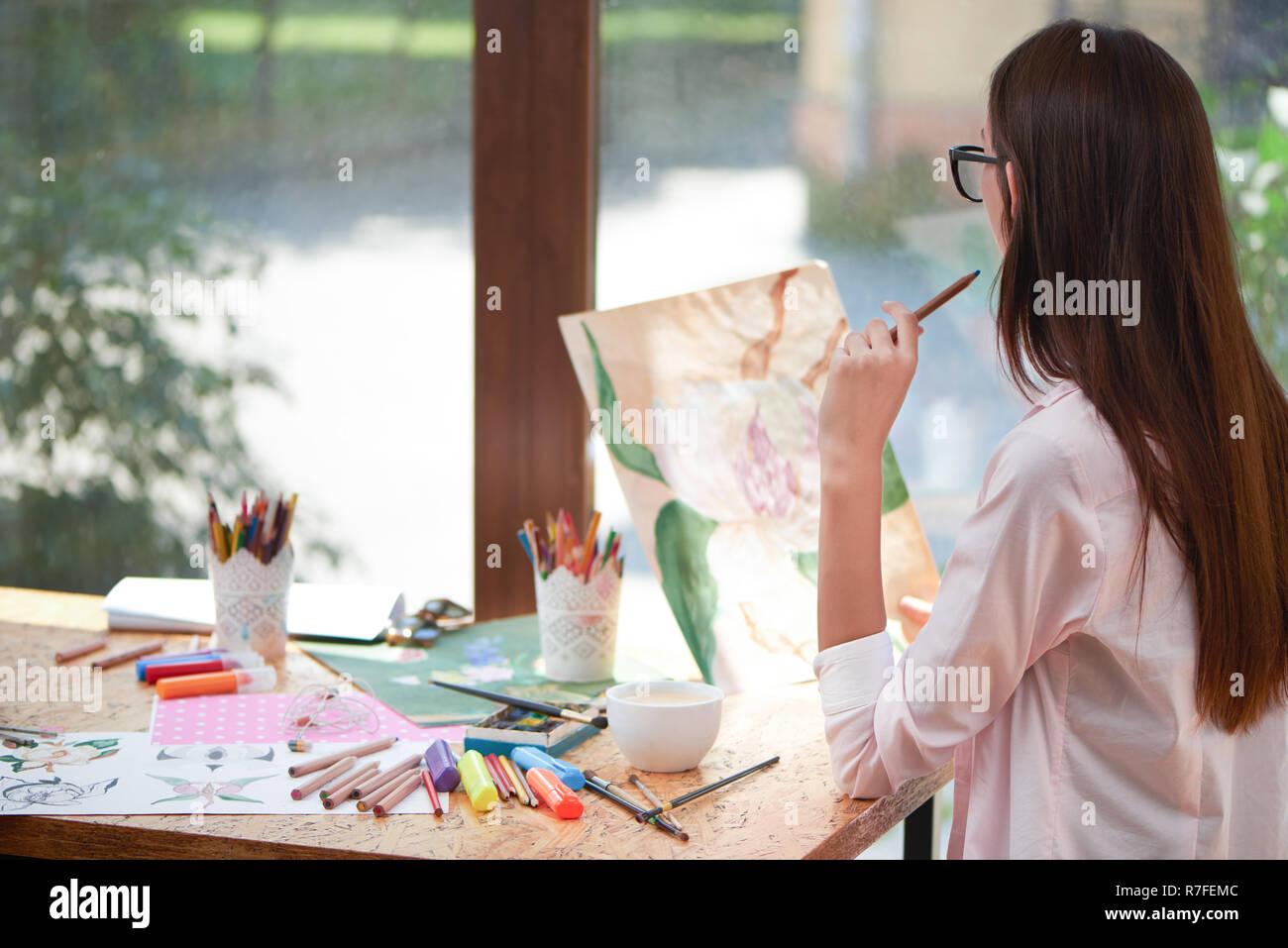 Jeune artiste à photo de fleur et la pensée. Méconnaissable woman holding crayon en main. Fille assise à table avec les fournitures du peintre comme marqueurs, brosses et feuilles de papier. Banque D'Images