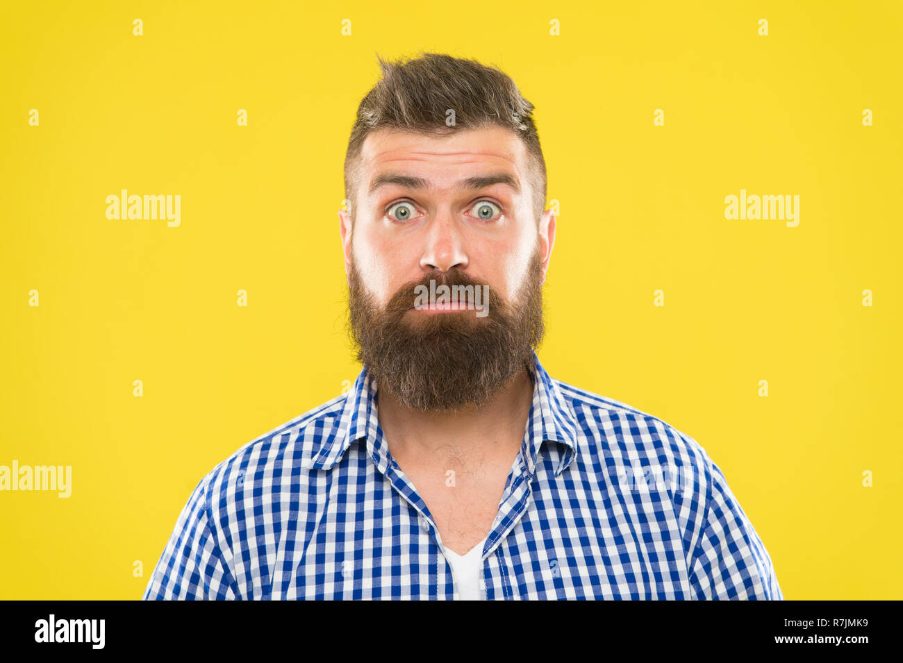 Nouvelles surprenantes. Hipster barbu homme demande face à fond jaune close up. Guy surpris face à l'expression. Hipster avec barbe et moustache expression émotionnelle surpris. Macho surpris rustique. Photo Stock
